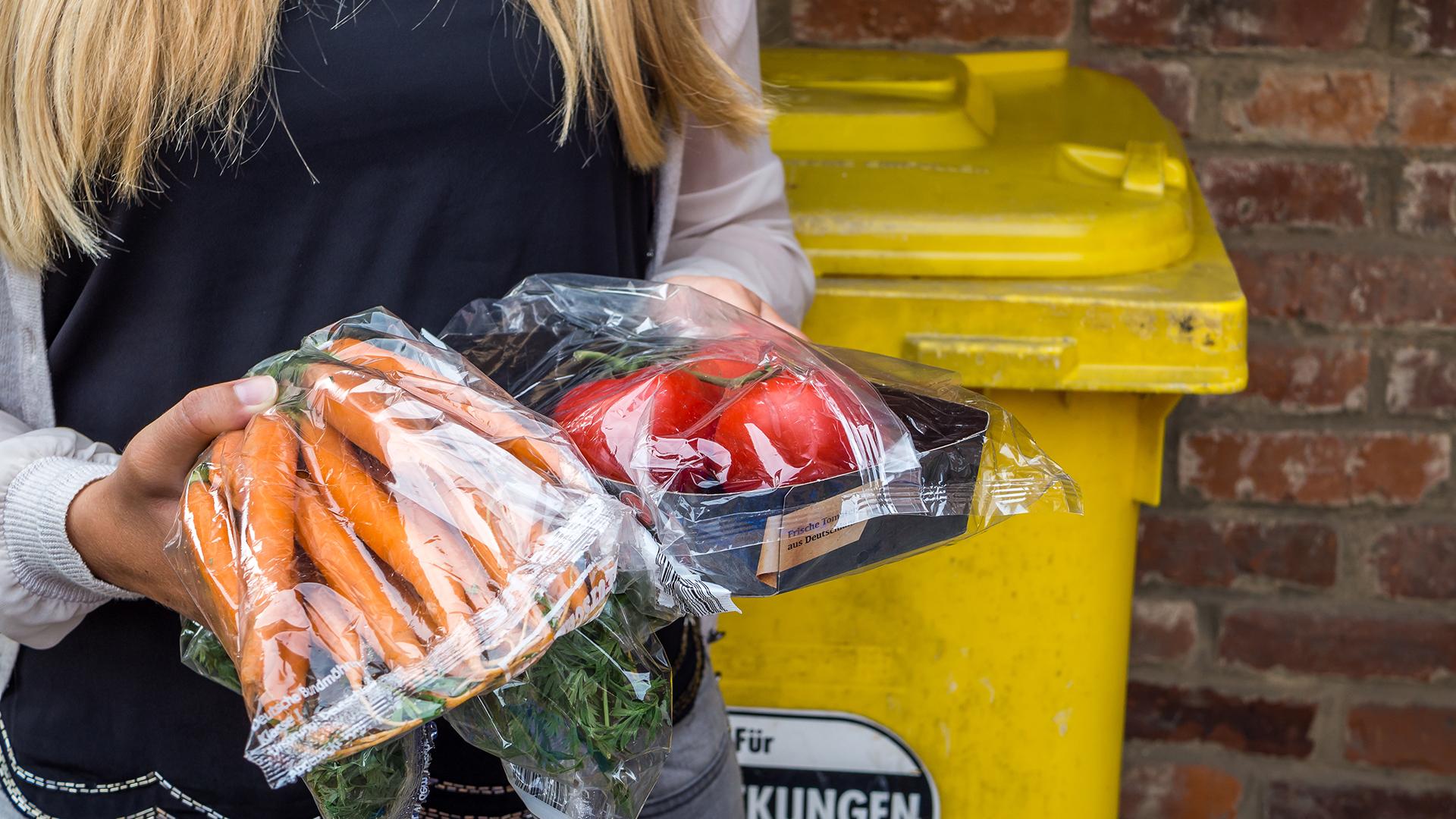 Eine Frau vor einer Mülltonne hält Lebensmittel in der Hand.