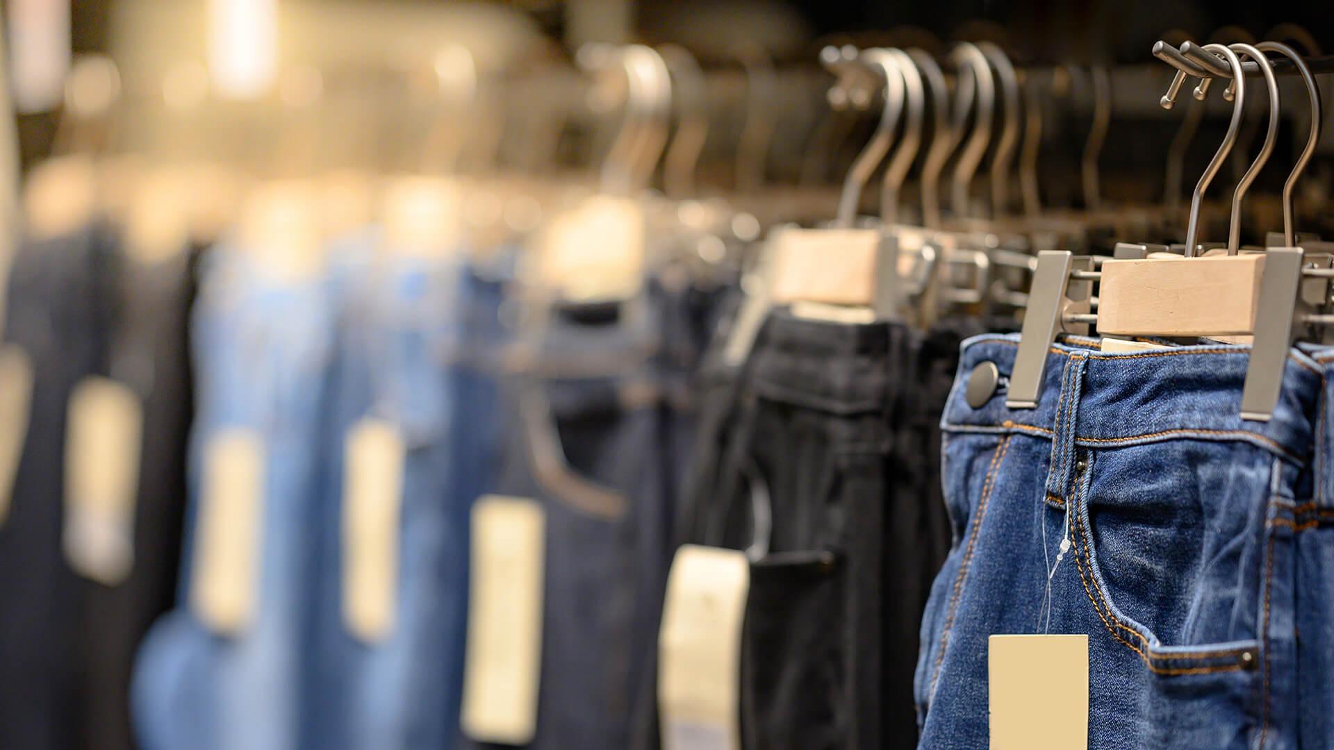 Verschiedene Jeans an Kleiderbügeln