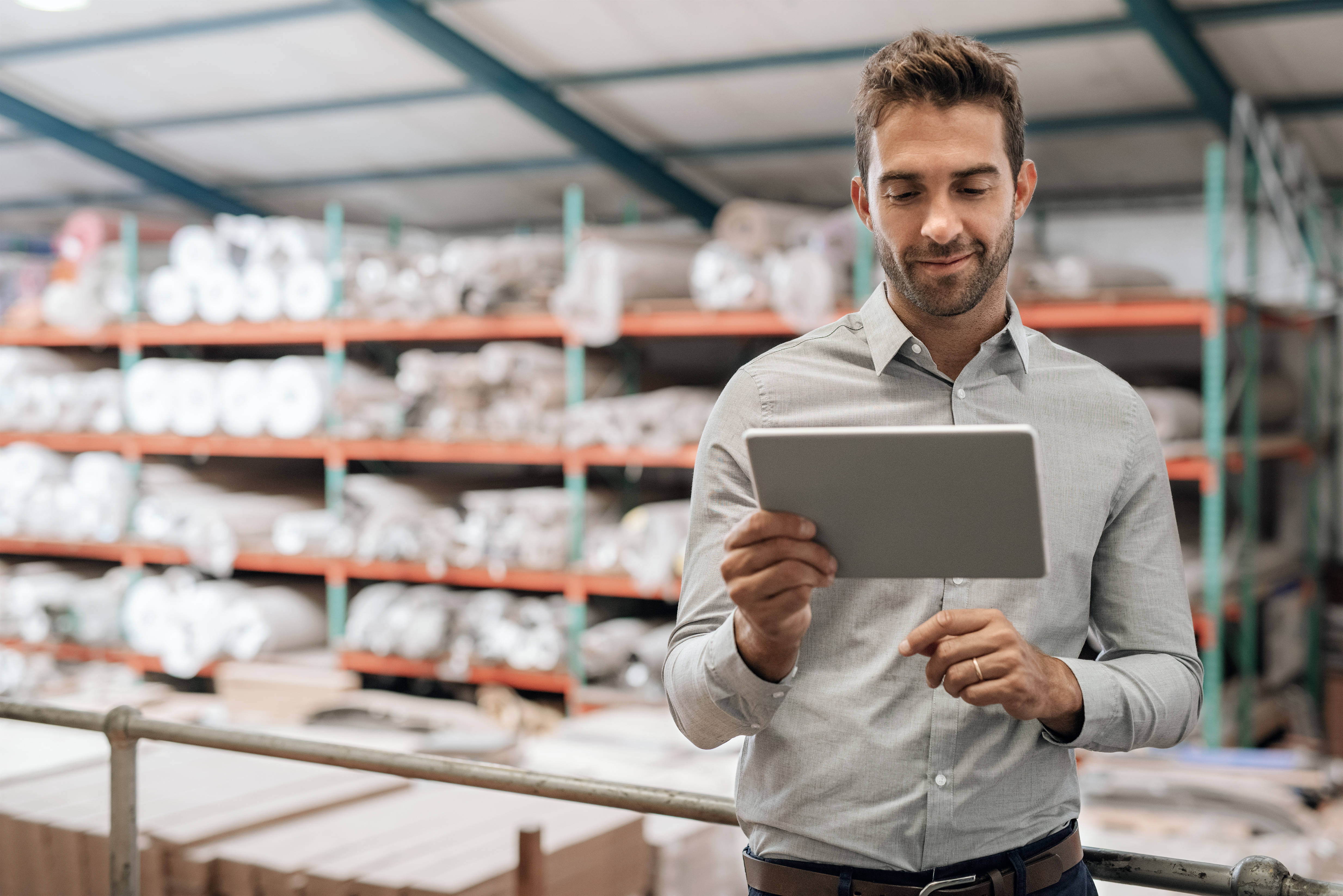 Smiling manager using a digital tablet in his warehouse