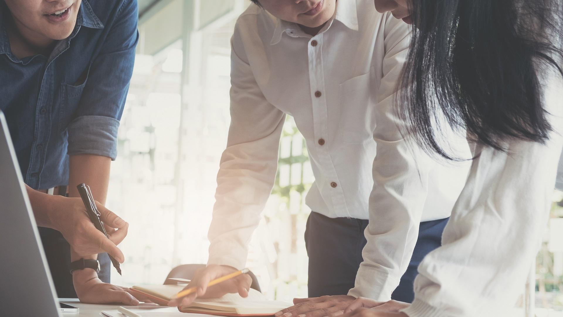 Drei Mitarbeiter stützen sich auf Tisch ab während einer Besprechung
